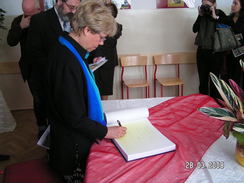 Pani Danuta Kuroń wpisuje się do księgi pamiątkowej po uroczystości nadania imienia